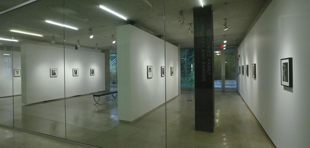 View of a gallery space with white walls and black and black and white photos in black frames on the walls.