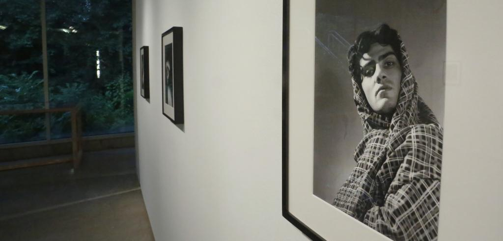 An oblique angle of a gallery wall with a close up view of a black and white photographic portrait on the right and two other framed pictures in the background.