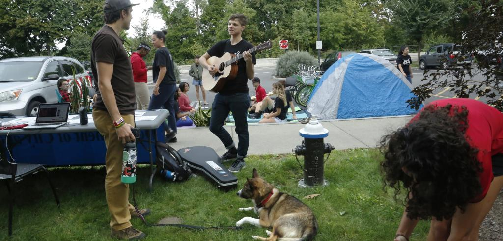 Man in center of picture plays a guitar while talking to another man with a dog on a leash.