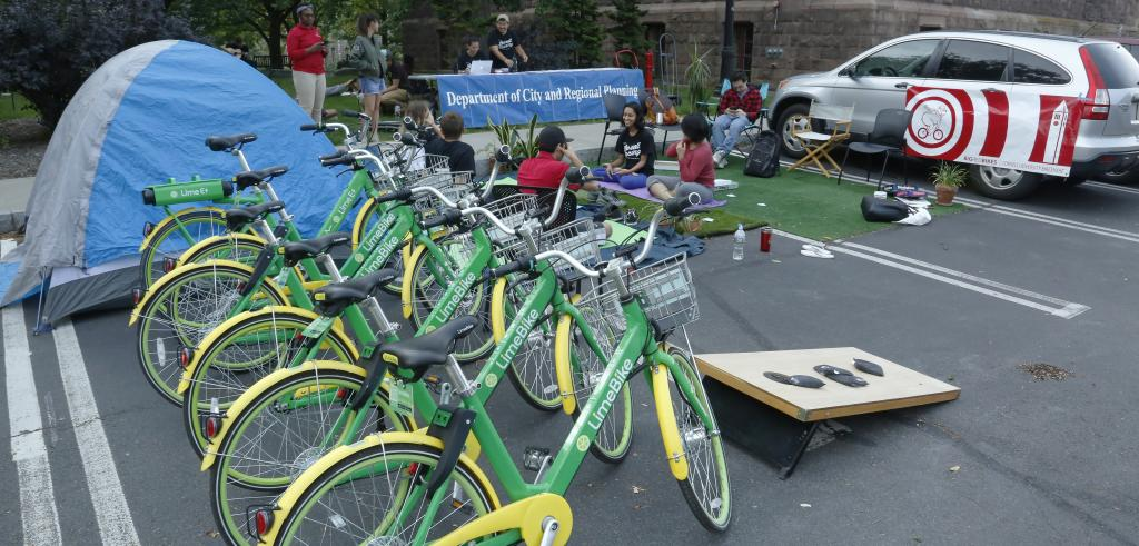 Green and yellow bicycles on the right side of the photo with a blue banner in the background and a red and white banner hanging on a silver car on the right, with people sitting in the center of the picture.