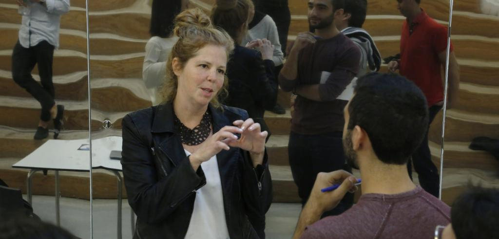 Woman speaking to man gesturing with her hands.