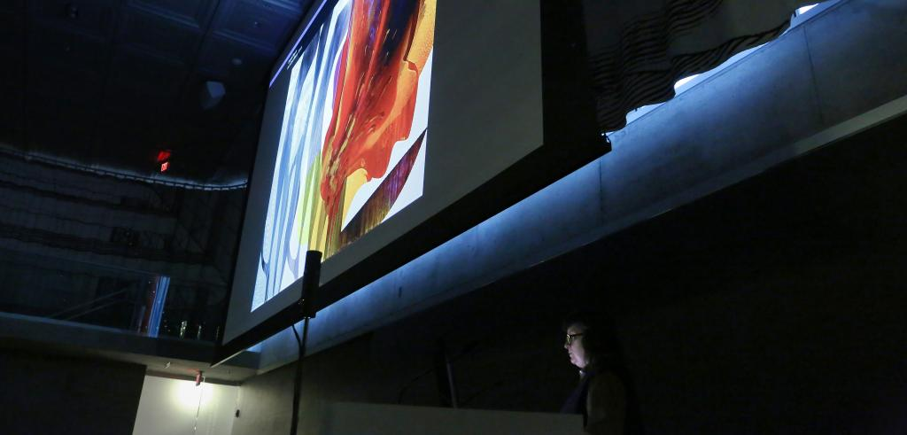 A projection screen showing a bright color painting with womans face below.