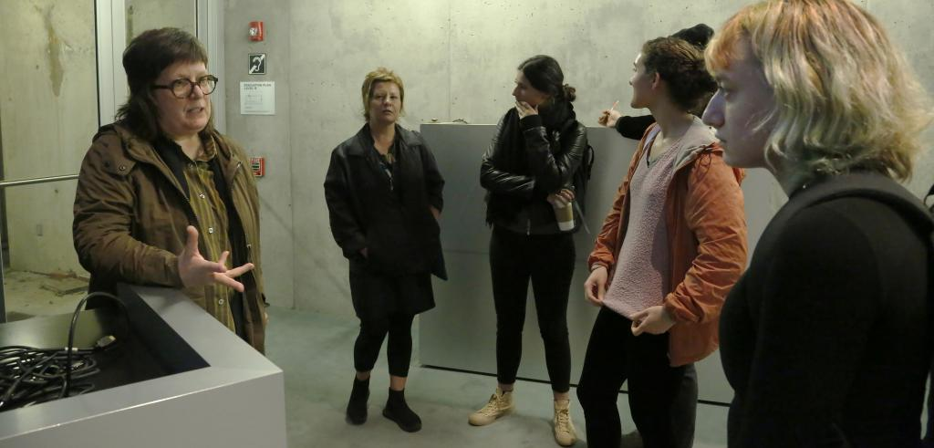 Woman with glasses interacting with a group of people.