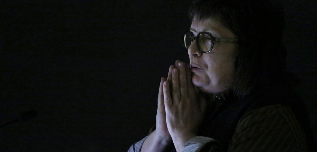 Woman wearing glasses with hands resting in front of her chin.