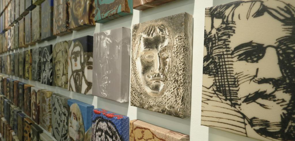 Images of sculpted faces on stretched canvas.