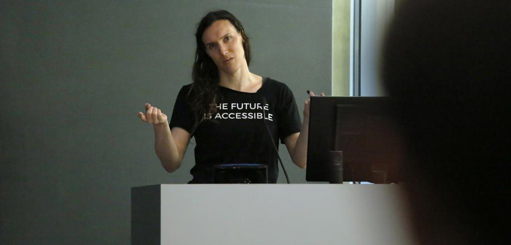 Woman gesturing from a lectern.