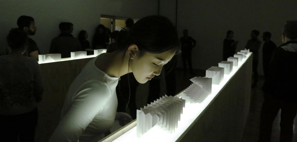 Woman looking at a model in an exhibition.