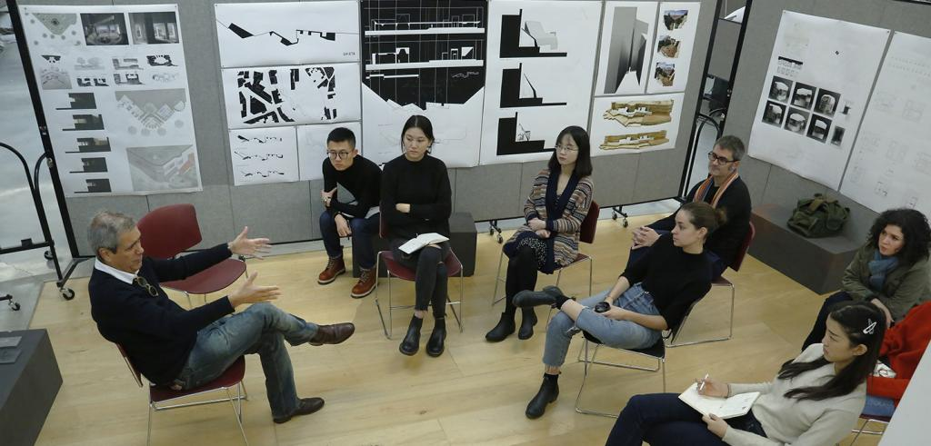 People sitting in a room discussing architectural drawings