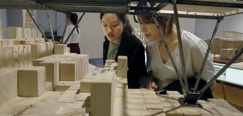 Two women study a model made of wood and steel.