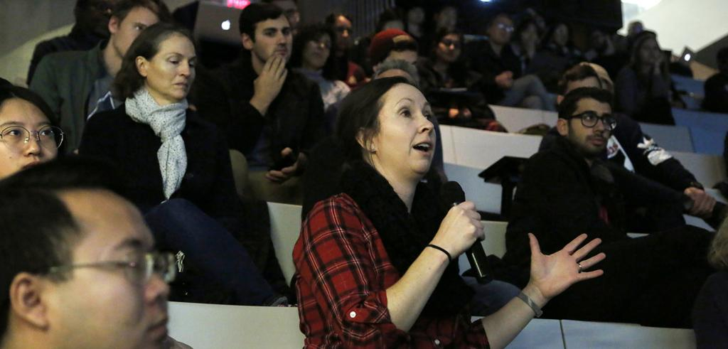 Woman in audience holding microphone and speaking.