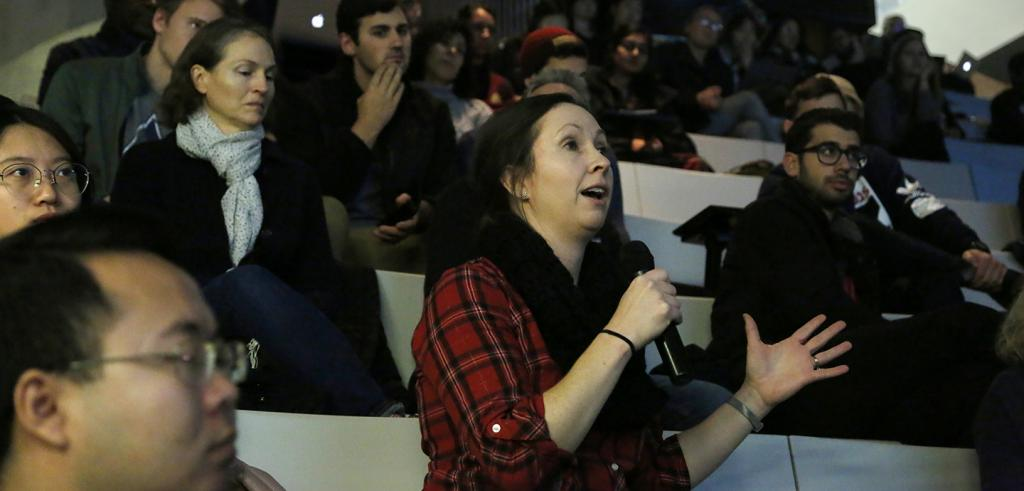 A woman speaking into a microphone among people seated in an auditorium