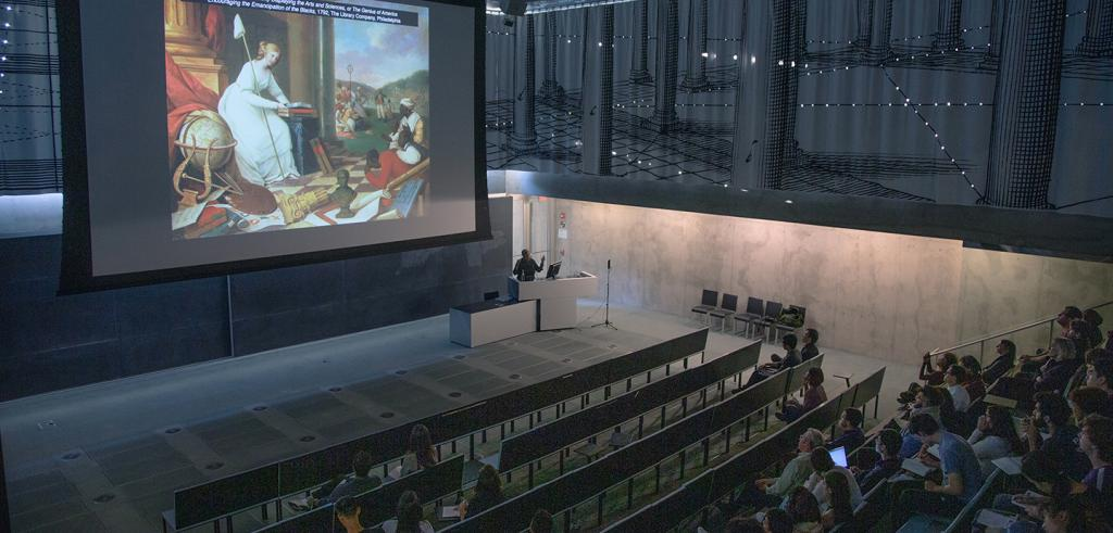People in an auditorium with an image projected on a very large screen.