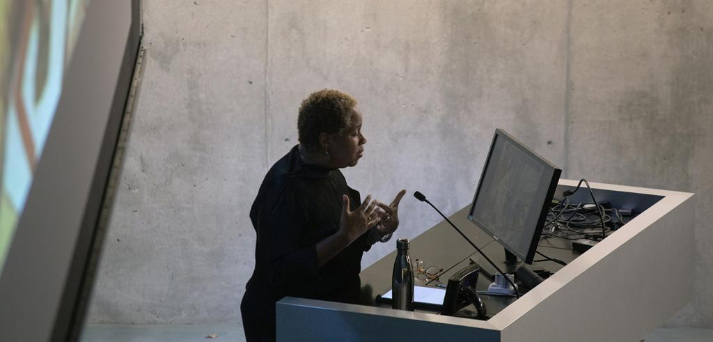 Woman at a lecturn gesturing, while viewing a monitor on a lectern