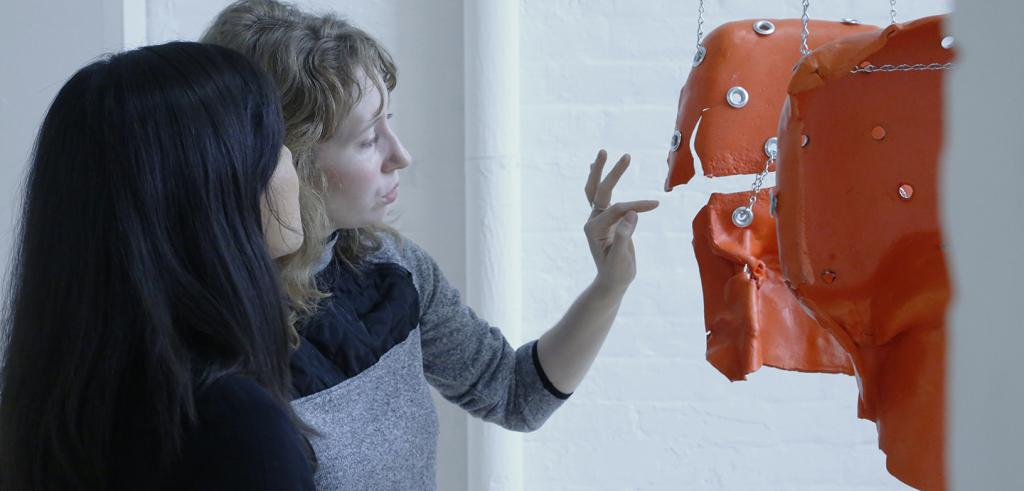 two women examine an orange-colored sculpture suspended from chains