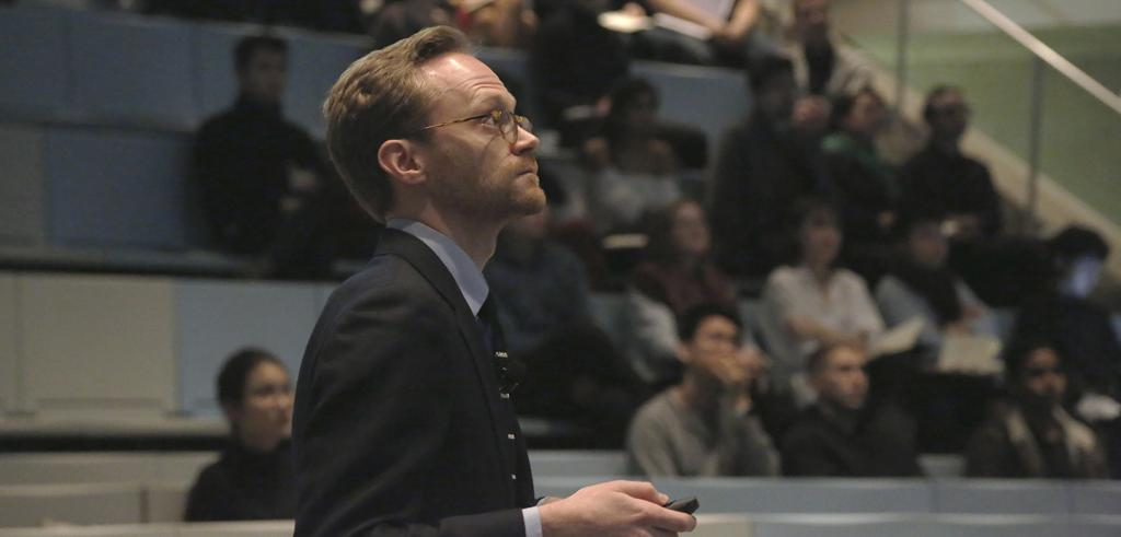 Man with glasses and people sated in an auditorium behind him.