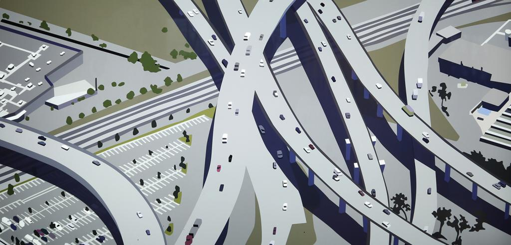 An aerial view of cars moving over a maze of gray and green roads.