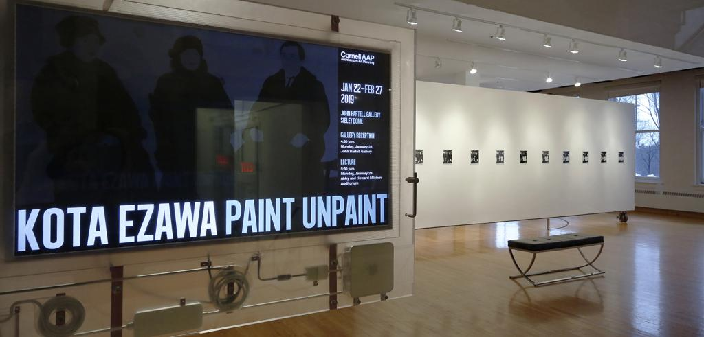 A view of a gallery with an LCD screen in the left side of the frame.