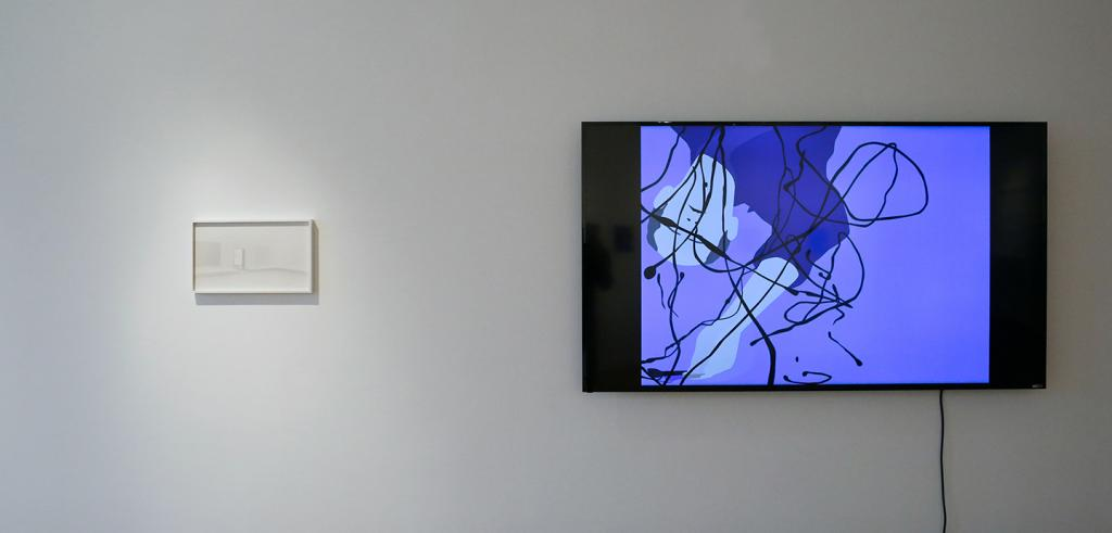 An LCD screen and a white framed image on a gallery wall.