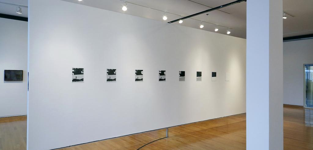 A row of eight square prints on a white wall in a gallery