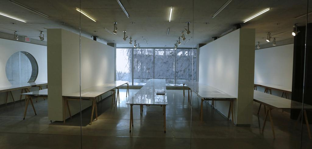 A gallery with white walls and tables