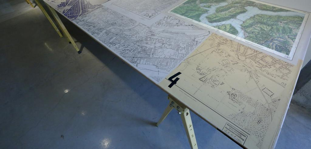 A table with maps and renderings