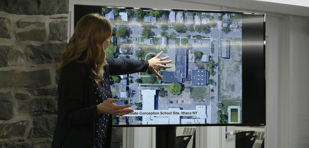 A women gesturing at an aerial photo of buildings projected on an LCD flat panel screen