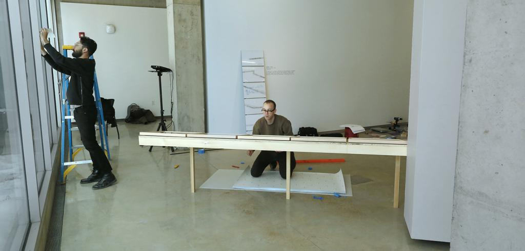 Two men installing an exhibit in a gallery.