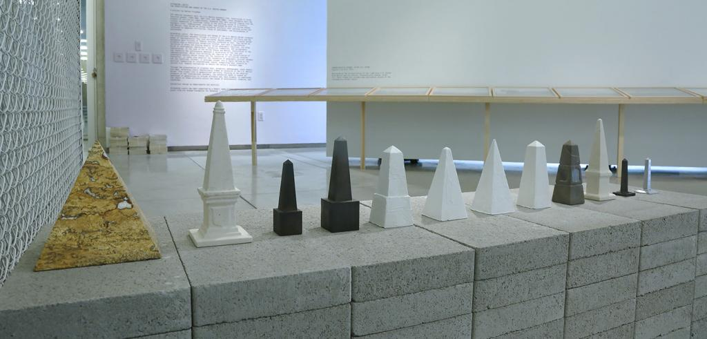 12 models obelisk monuments arranged in a row on cinder blocks.