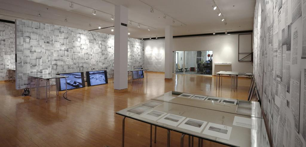 Table displays, LCD panels, and walls covered with printed papers in an art gallery.