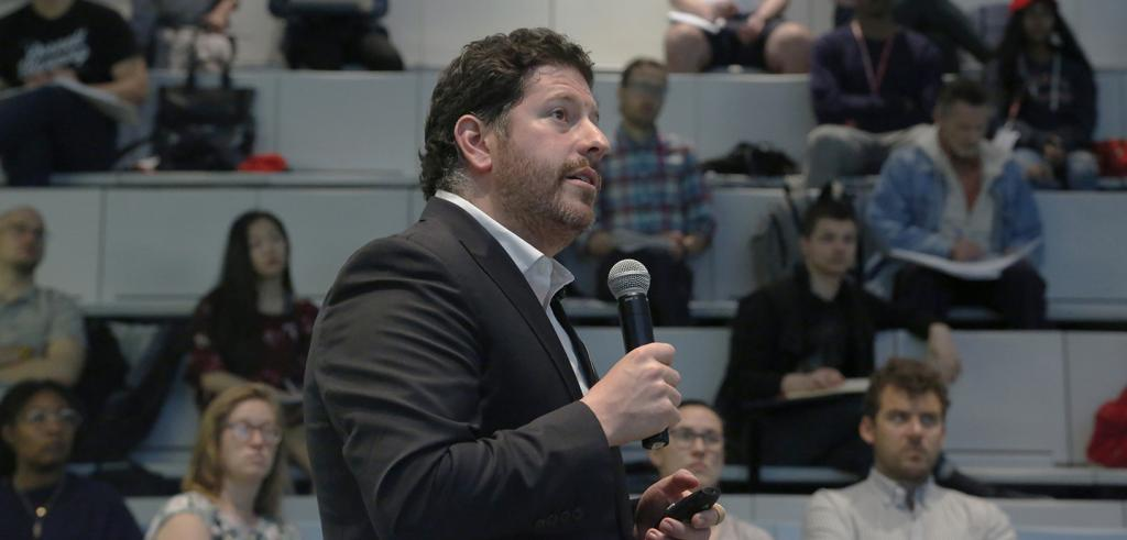 Man holding a microphone lecturing in an auditorium.