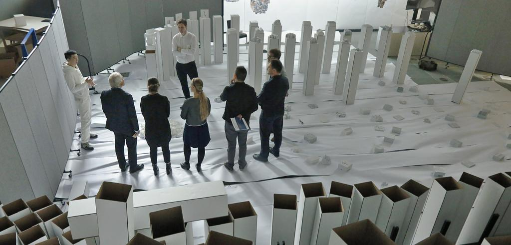 A group of people converse while standing surrounded by dozens of shoulder-height, white vertical columns