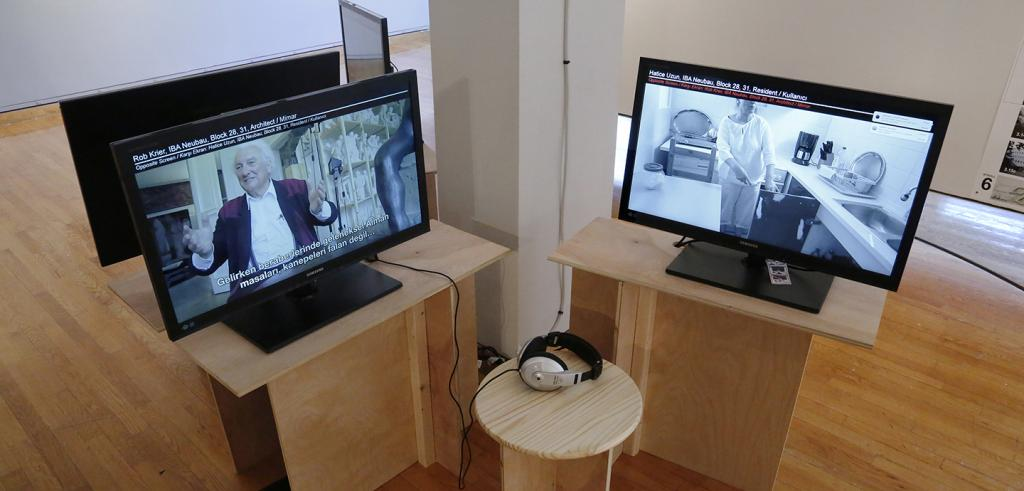 Two monitors on pedestals with headphones attached