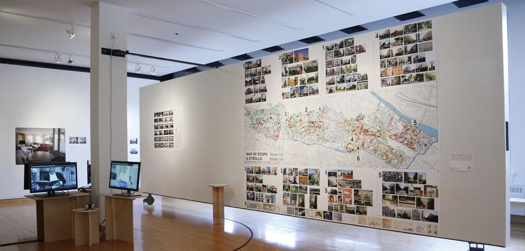 An exhibit with maps and photos on a wall, and video monitors.