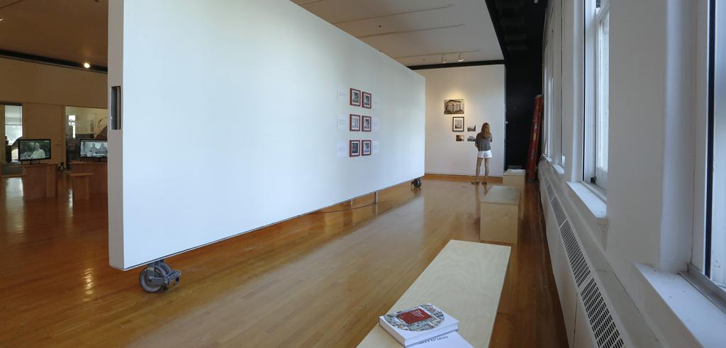 Six framed imges on a gallery wall and a book resting on a bench