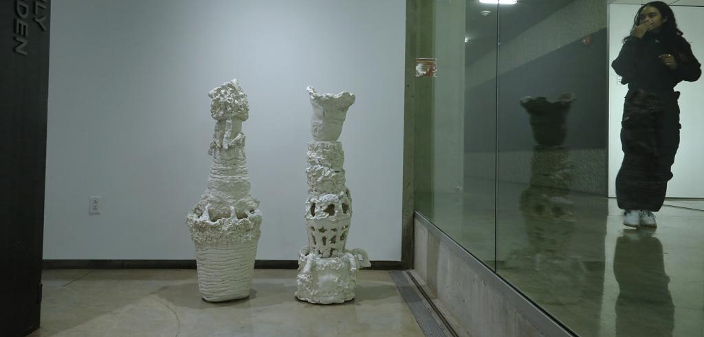 Ceramic sculptures with a figure and reflections in glass.