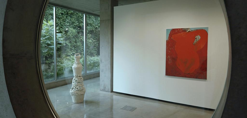 A view of a gallery with a painting and a sculpture.