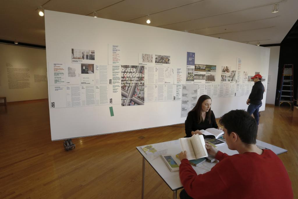 People seated at a table reading books and viewing designs posted on a wall