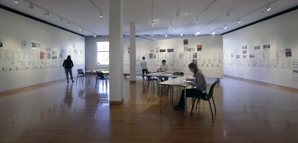 A view of a gallery exhibition with people seated and standing in the space