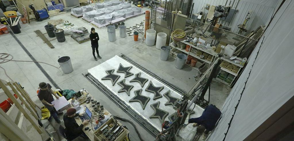 A large interior space with people, industrial supplies, and machinery printing concrete shapes