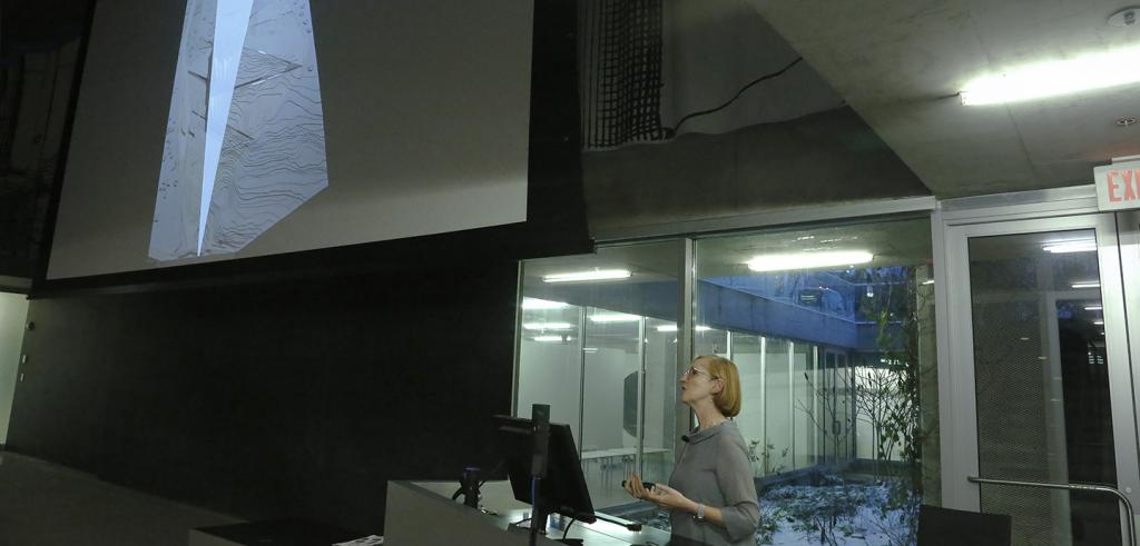 Woman looking out from behind a podium, with an image projected on a screen.