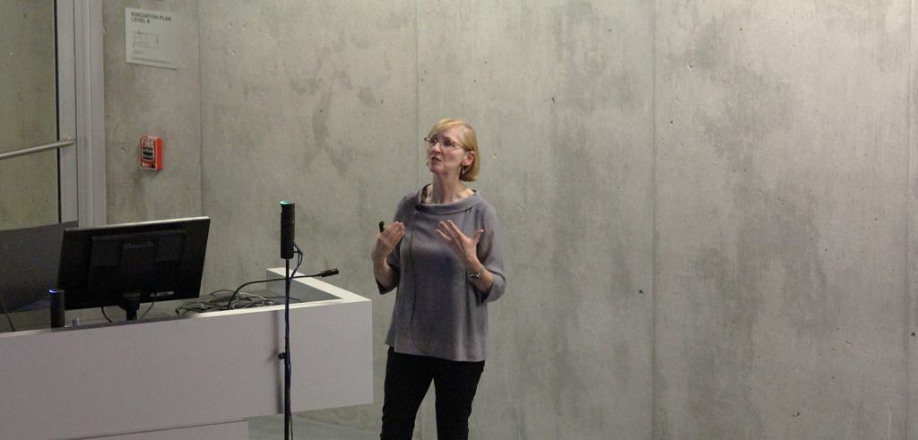 Woman gesturing with her hands, standing in front of a concrete wall.