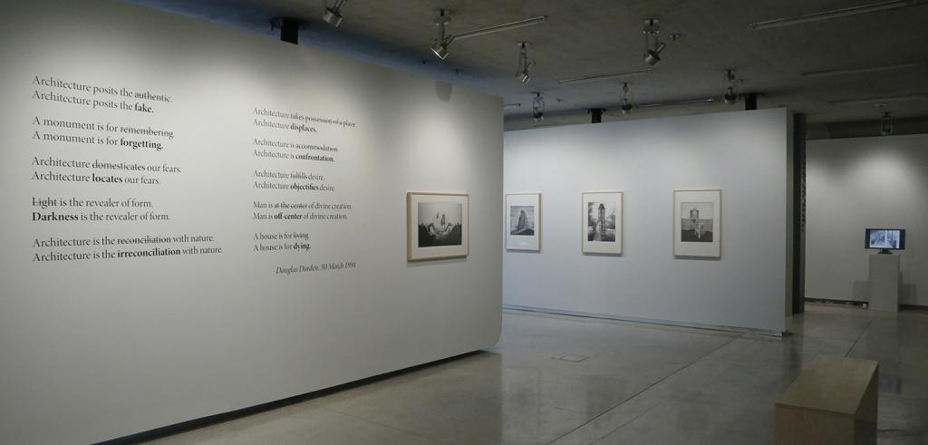 View of an art gallery with framed images and text on white walls and monitor on a pedestal.