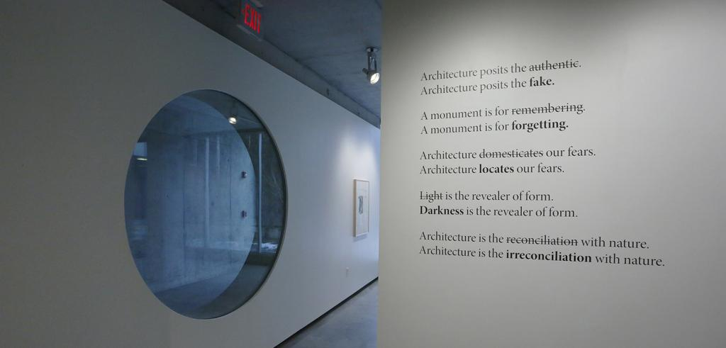 An oblique view of two art gallery walls with text on the right and a round window on the left.