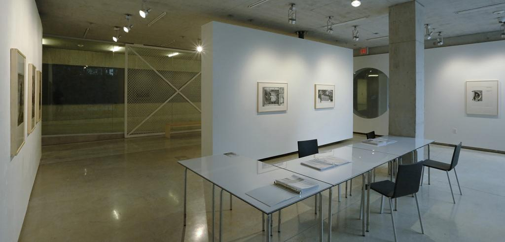White gallery walls with binders of images on tables and chairs in the forground.