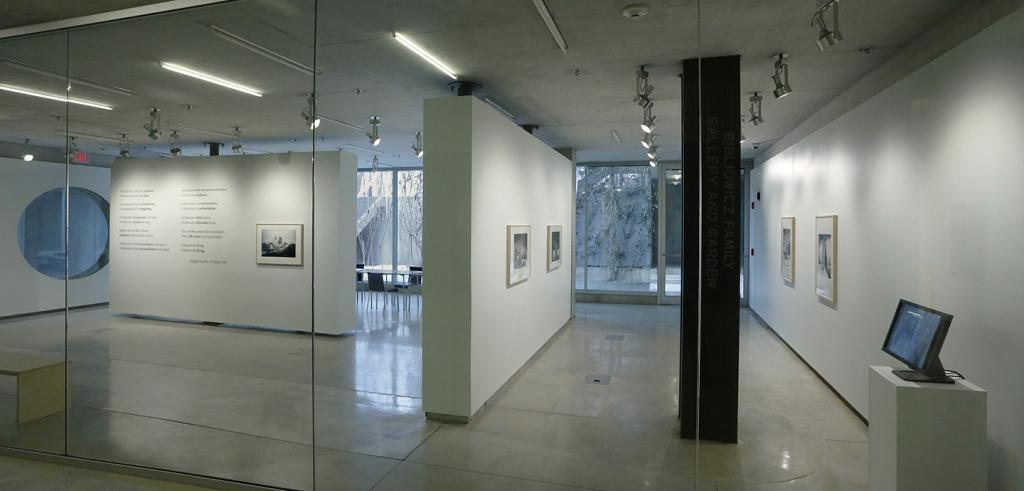 Galss and white gallery walls with framed images and text and a computer monitor on a pedestal.