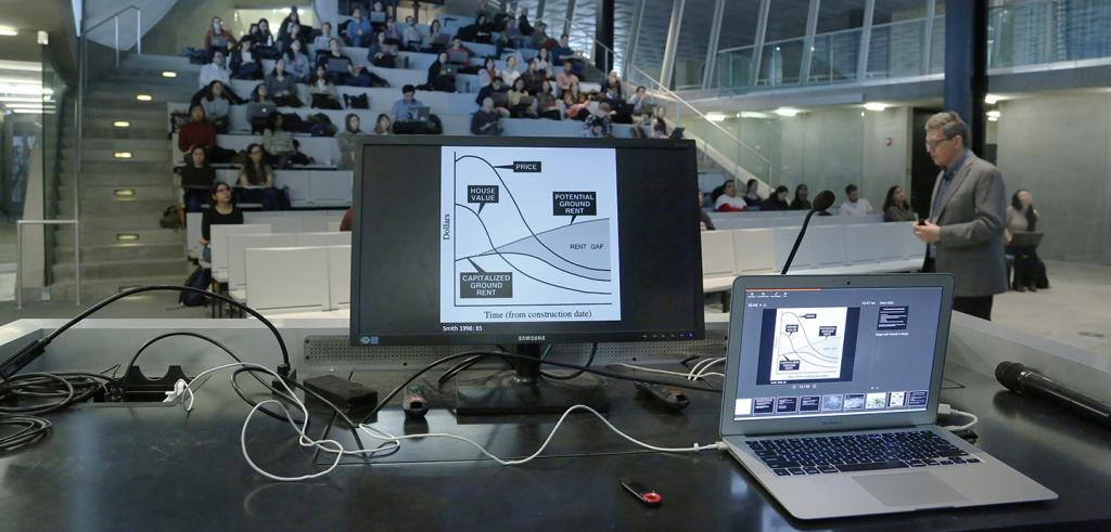 Two computer screens on a podium, with people sitting in an auditorium and man walking on right.