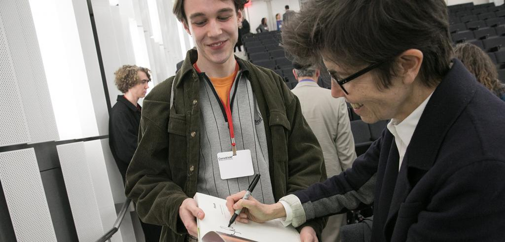 Young man on the left holds a paper while woman signs her autograph
