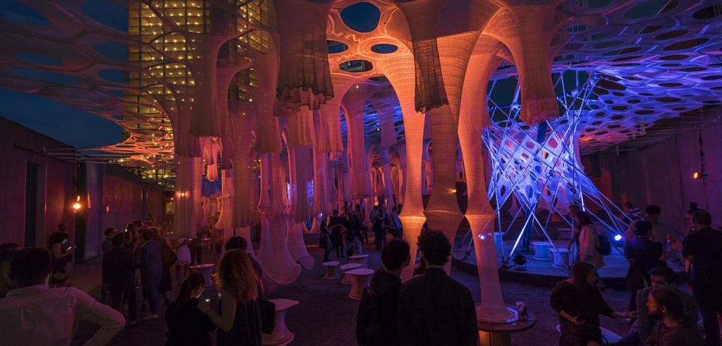 Tubular fabric structures suspended above a courtyard at night