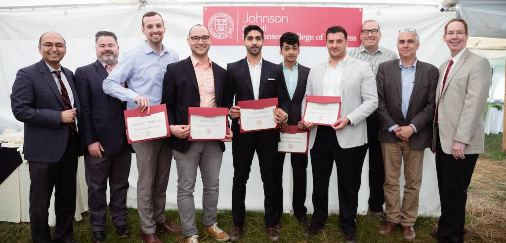 Ten men in a row in business casual clothing, some holding award certifcates