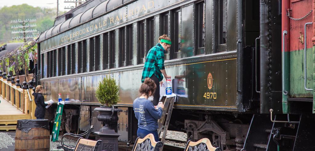 three students clean the exterior of an old railroad car